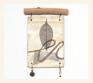 Mixed media wall hanging by Clare Rosen. Reclaimed plywood, leaf, found branch, wire, beads. Copyright 2018.